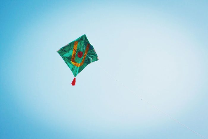 A colorful kite flying in the sky during the Uttarayan International Kite Festival