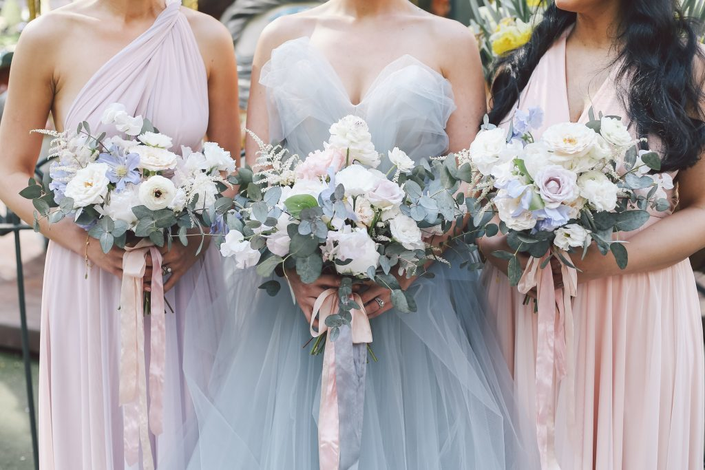Bride and bridesmaids in shades of pastel pink, blue, and purple