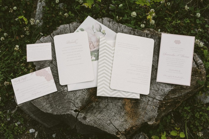 Floral letterpress wedding invitations with chevron invitation sleeves from Smock