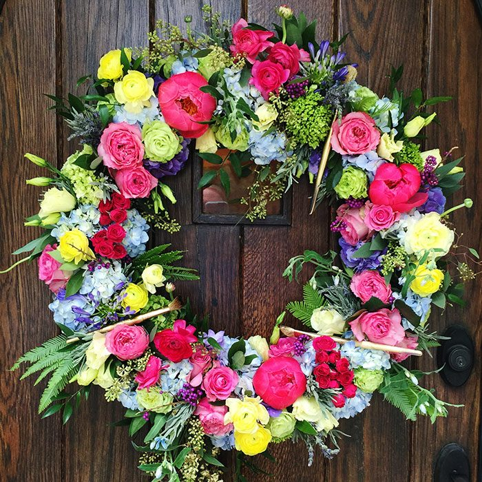 Vibrant floral wreath with paintbrushes | Paint party decor