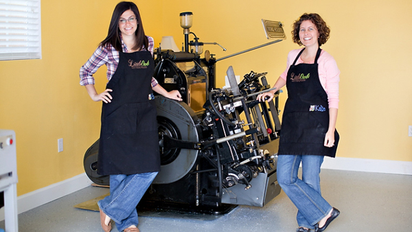 Gina and Katie Vallecorsa of LittleOwl Letterpress in front of their Heidelberg Windmill.