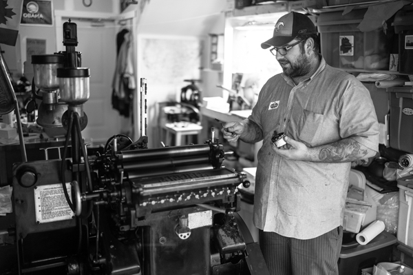Travis Deglow of Port Paper Co checks out his beloved printing press.