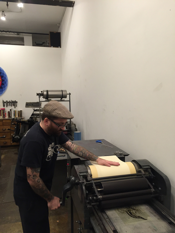 John Reardon printing on a Vandercook and pulling the paper through the press.