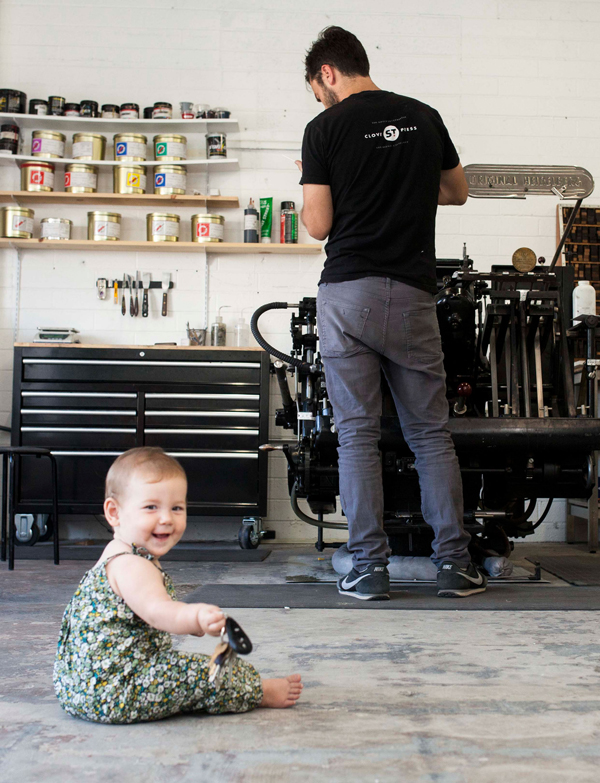 "A young ""printer-in-training"" watches Daniel Heffernan print at Clove St. Press."