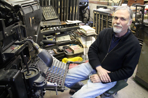 Tim Fay of Route 3 Press sits with his linotype.